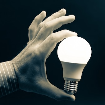 Main humaine tenant la lampe à led incluse sur un fond sombre. industrie électrique industrielle. technologies électroniques modernes