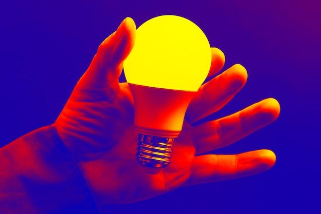 Main humaine tenant la lampe à led incluse sur un fond sombre. technologies électroniques modernes