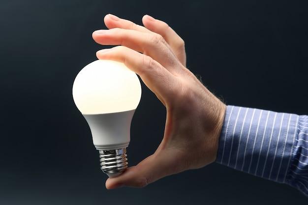 Main humaine tenant la lampe led incluse