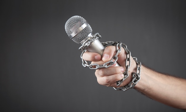 Main humaine tenant un microphone attaché avec des chaînes.