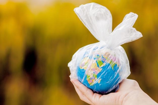 La main humaine tient la planète terre dans un sac en plastique. le concept de pollution par les débris plastiques. réchauffement climatique dû à l'effet de serre.