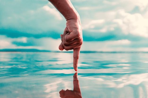 La main humaine touche l'eau sur la rivière, la crise de l'eau