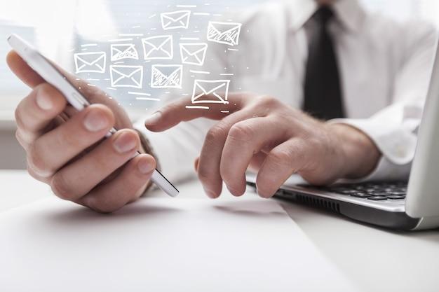 Main humaine travaillant sur smartphone avec illustration de symbole de courrier