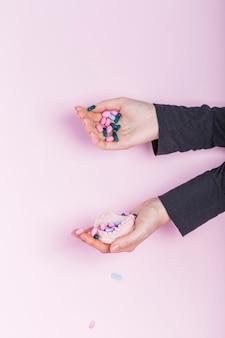 Main humaine, verser des pilules en plâtre modèle dentaire jeté sur fond rose