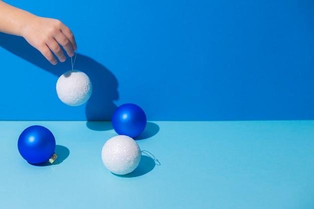 La main d'image abstraite tient des décorations d'arbre de noël sur un fond bleu.