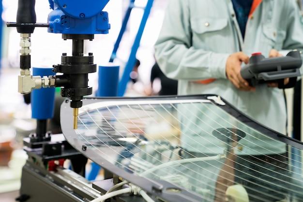 Main d'ingénieur à l'aide d'une tablette, machine de bras de robot d'automatisation lourde dans une usine intelligente