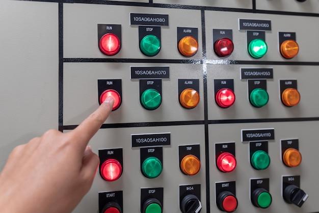 Main de l'ingénieur travaillant et vérifier la distribution d'énergie électrique de l'appareillage de commande dans la salle du poste