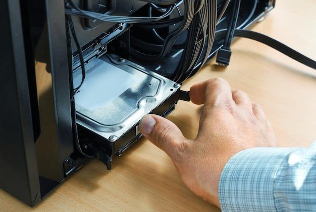 La main insère la mémoire du disque dur dans l'unité centrale de l'ordinateur