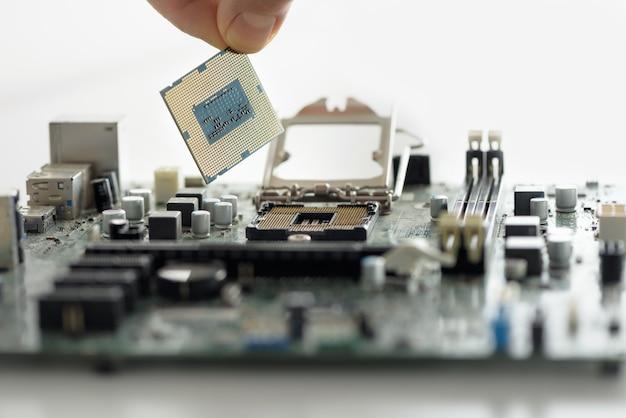 La main installe le processeur sur la carte mère en gros plan