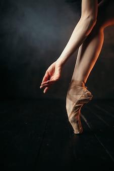 Main et jambes de ballerine en pointes, parquet noir. ballerine en robe rouge et noir pratique de la danse sur la scène du théâtre