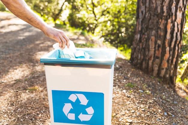 Main jetant les ordures dans la poubelle dans la forêt