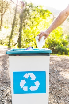 Main jetant des ordures dans la poubelle de recyclage