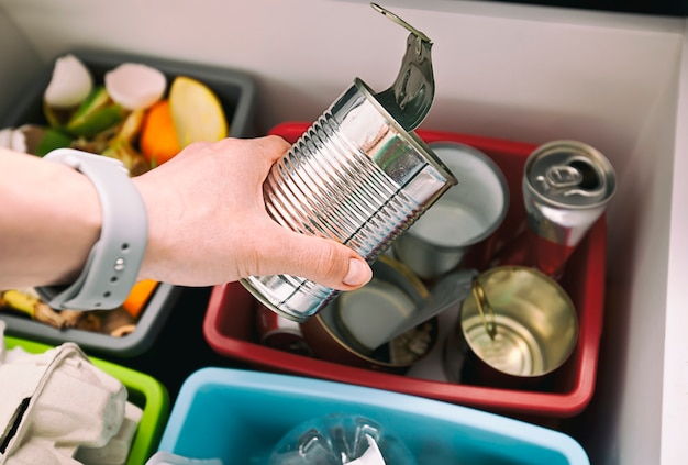 Main jeter la boîte de conserve dans l'un des quatre conteneurs pour trier les ordures