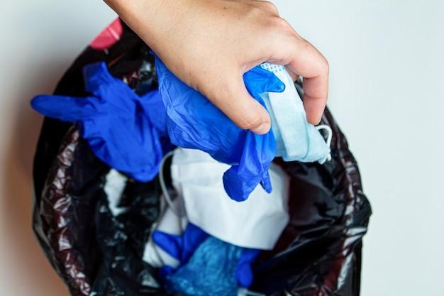 Main jeter les gants médicaux et les masques de protection jetés à la poubelle après la quarantaine