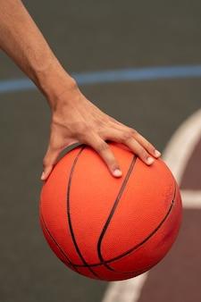 Main de jeune basketteur actif tenant le ballon tout en se préparant à le lancer pendant le match sur le terrain