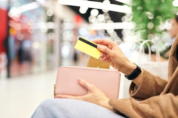 Main de jeune cliente contemporaine mettant la carte en plastique dans le portefeuille tout en se reposant dans l'environnement du centre commercial après le shopping