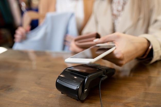 Main de jeune femme accro du shopping tenant smartphone sur machine de paiement sur le comptoir lors de l'achat de nouveaux vêtements en boutique