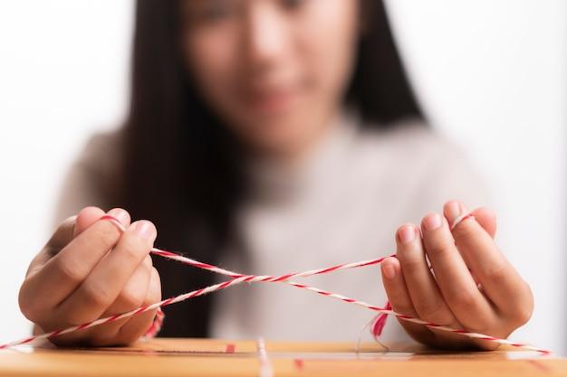 Main jeune femme d'affaires propriétaire adolescent attachant une corde préparant le colis
