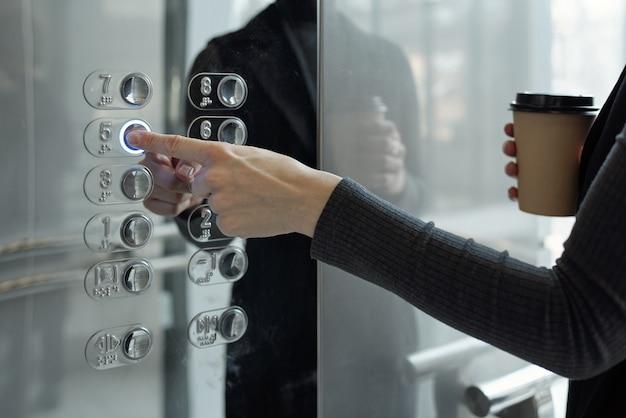 Main de jeune femme d'affaires avec un verre en poussant le bouton à l'intérieur de l'ascenseur tout en retournant au bureau au cinquième étage à la pause-café