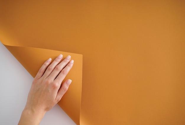 Main d'une jeune femme avec une belle manucure sur fond blanc et beige. manucure féminine. avec place pour le texte, vue de dessus, pose à plat.