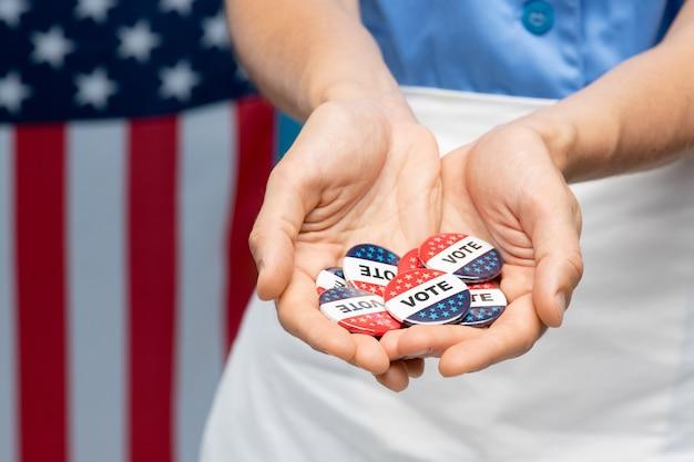 Main de jeune femme de chambre en uniforme ou femme au foyer montrant un groupe d'insignes de vote contre stars-and-stripes en