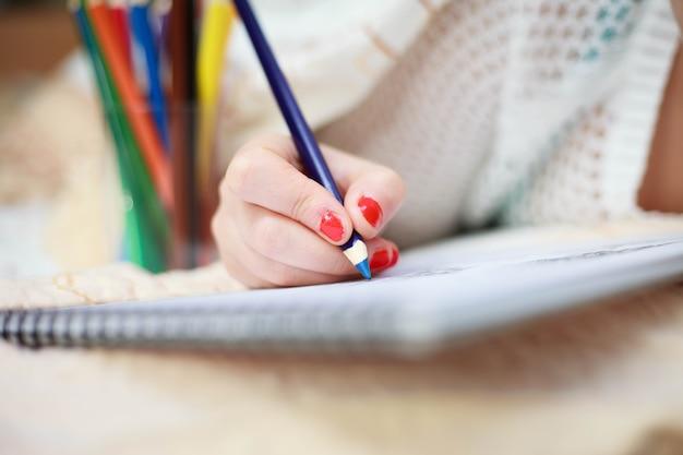 Main de jeune femme dessin photo d'art par des crayons colorés