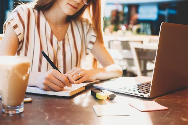 Main d'une jeune femme prenant des notes tout en travaillant à l'extérieur dans un café.