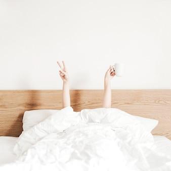 Main de jeune femme avec tasse de café au lit avec des draps blancs.