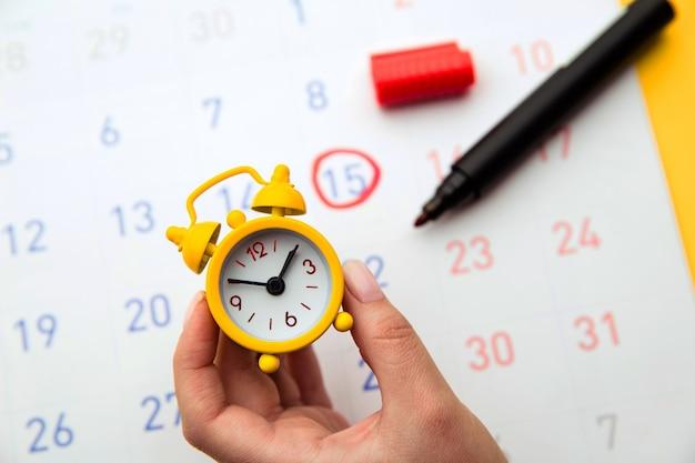 Main de jeune femme tenant une horloge jaune.