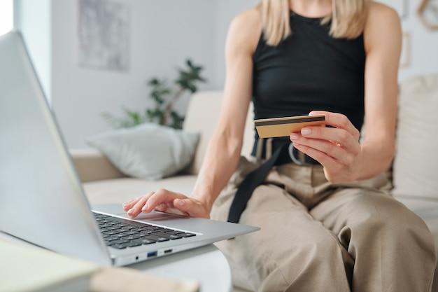 Main de jeune femme en tenue décontractée tenant une carte de crédit sur un clavier d'ordinateur portable et appuyant sur le bouton tout en surfant dans la boutique en ligne