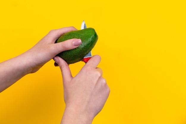 La Main De La Jeune Fille Coupe Un Avocat Mûr Avec Un Couteau Sur Fond Jaune Photo Premium