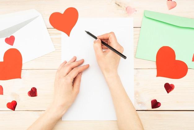 La main de la jeune fille écrit une lettre d'amour. la saint-valentin. carte de voeux à la main avec un coeur rouge en forme de figure. le 14 février est une célébration de célébration. vue d'en-haut