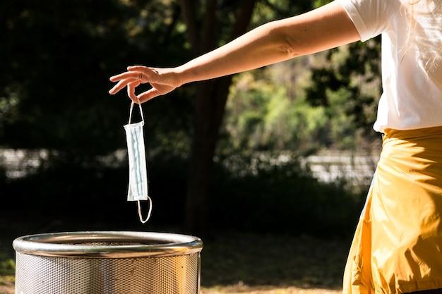La main de la jeune fille jetant un masque médical dans le bac à papier dans un parc. masque facial à usage unique. bonne façon de jeter le masque facial utilisé dans la poubelle. concept de coronavirus ou covid-19.