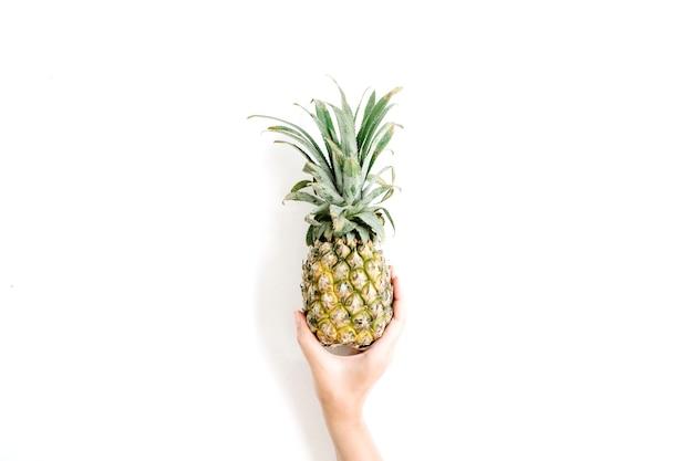 La main de la jeune fille tenant l'ananas.