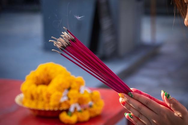 La main de la jeune fille tenant les bâtons d'encens pour demander des bénédictions aux choses sacrées.