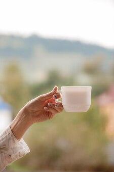 Main de la jeune fille tenant une tasse de café le matin, vue sur la montagne derrière, détente et journée de la liberté. mode de vie .