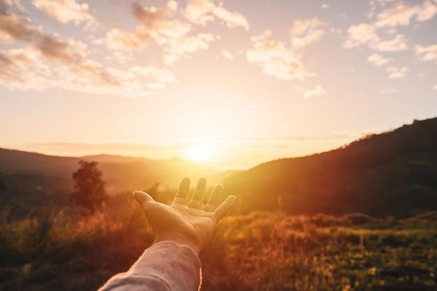 Main de jeune homme atteignant les montagnes pendant le coucher du soleil et beau paysage