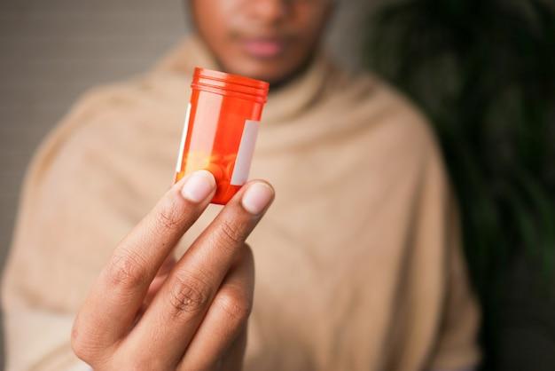 Main de jeune homme malade tenant le récipient de pilule de médecine