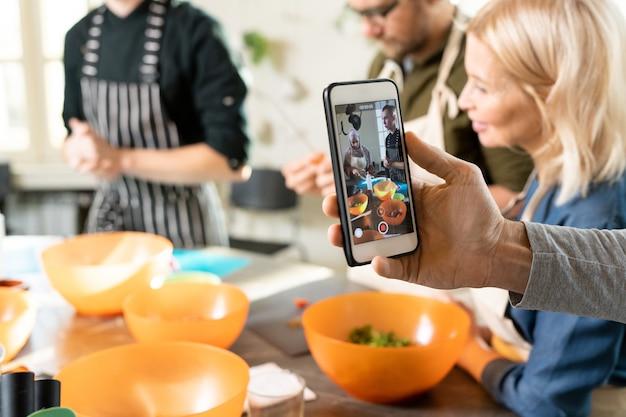 Main d'un jeune homme avec un smartphone filmant une vidéo d'une classe de maître de cuisine où un groupe d'apprenants fait de la pâte pour une délicieuse pâtisserie