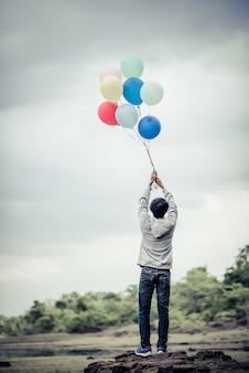 Main de jeune homme tenant des ballons colorés