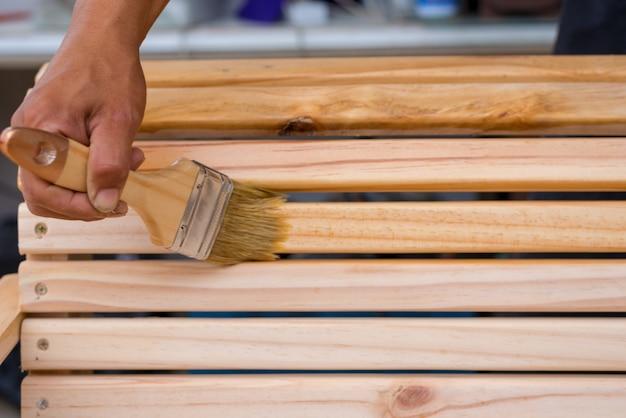 Main de jeune homme tenant une brosse en appliquant une peinture de vernis sur un meuble en bois