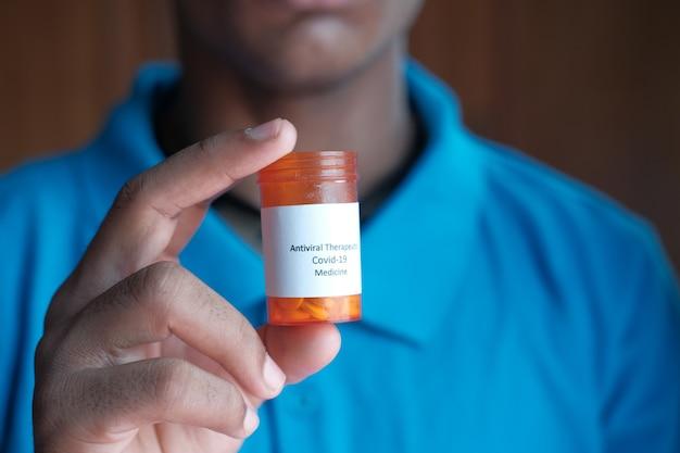 Main de jeune homme tenant le conteneur de pilules médicales covid