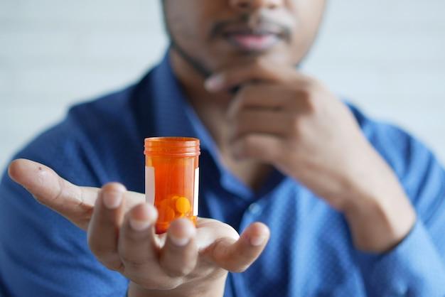 Main de jeune homme tenant le récipient de pilule de médecine situé blanc