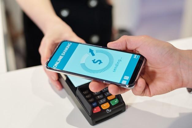 Main de jeune homme tenant un smartphone avec une page de banque en ligne pendant le processus de paiement sans contact dans un magasin, un supermarché ou un centre de loisirs