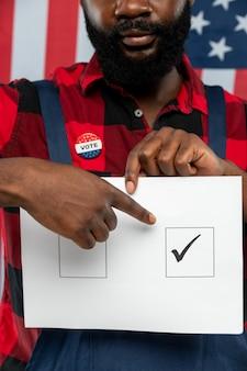 Main de jeune réparateur afro-américain pointant sur tique dans l'un des carrés sur le bulletin de vote en se tenant debout devant la caméra