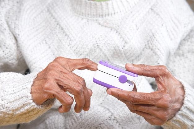 Main de jeunes femmes âgées à l'aide de l'oxymètre de pouls