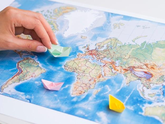 Main jouant avec des bateaux en papier sur la carte