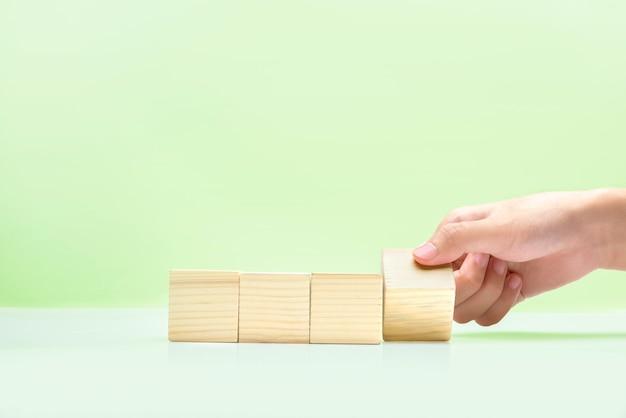 Main jouant avec bloc en bois