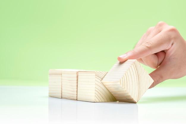Main jouant avec des blocs de bois sur la table