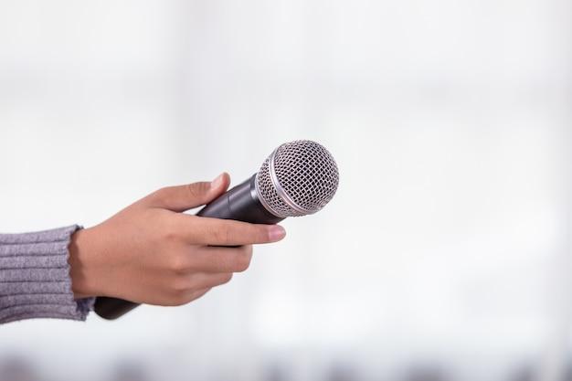 Main d'un journaliste tenant un nouveau microphone noir